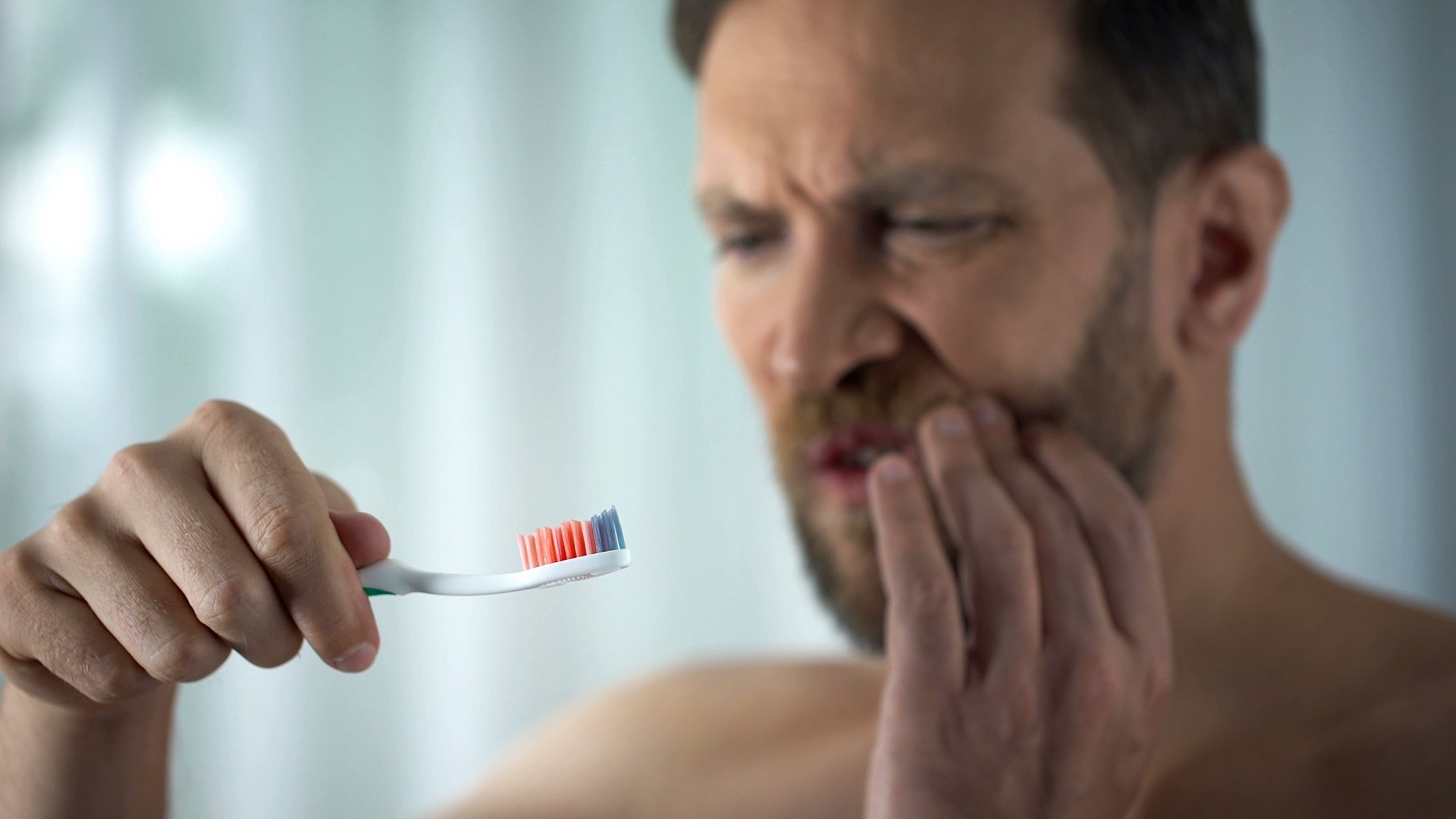 tooth decay symptoms True Dental man experiencing mouth soreness while looking at toothbrush