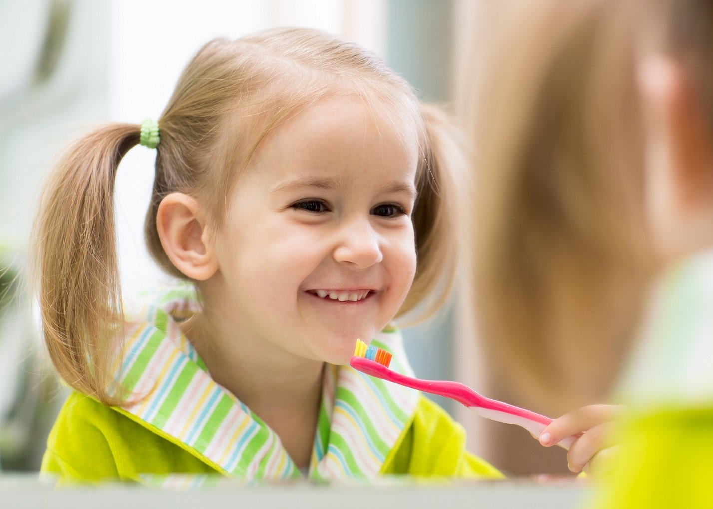 what is dental fluoride young child with toothbrush held up to her face looking happy