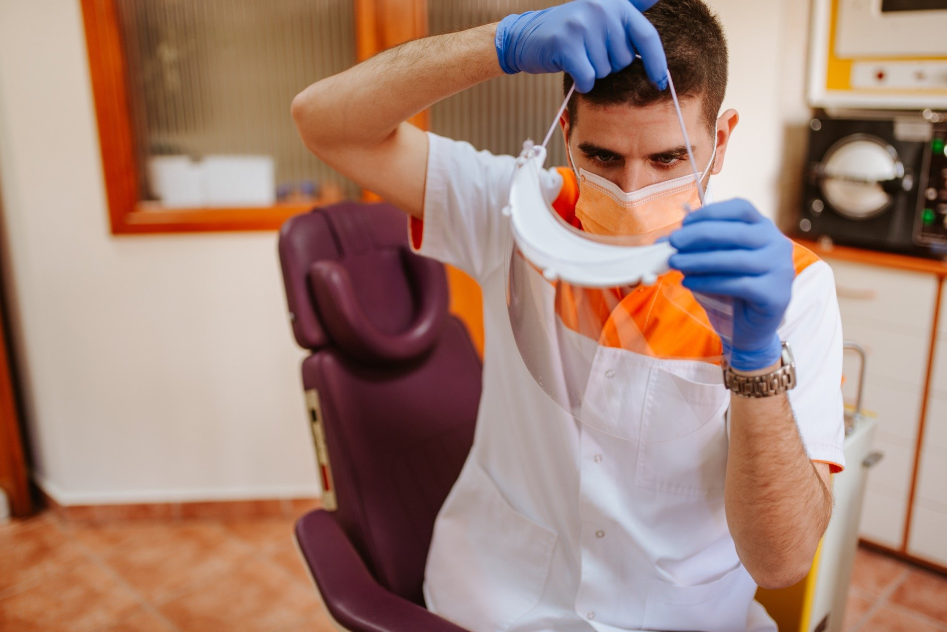 Kelowna dentist putting on face shield
