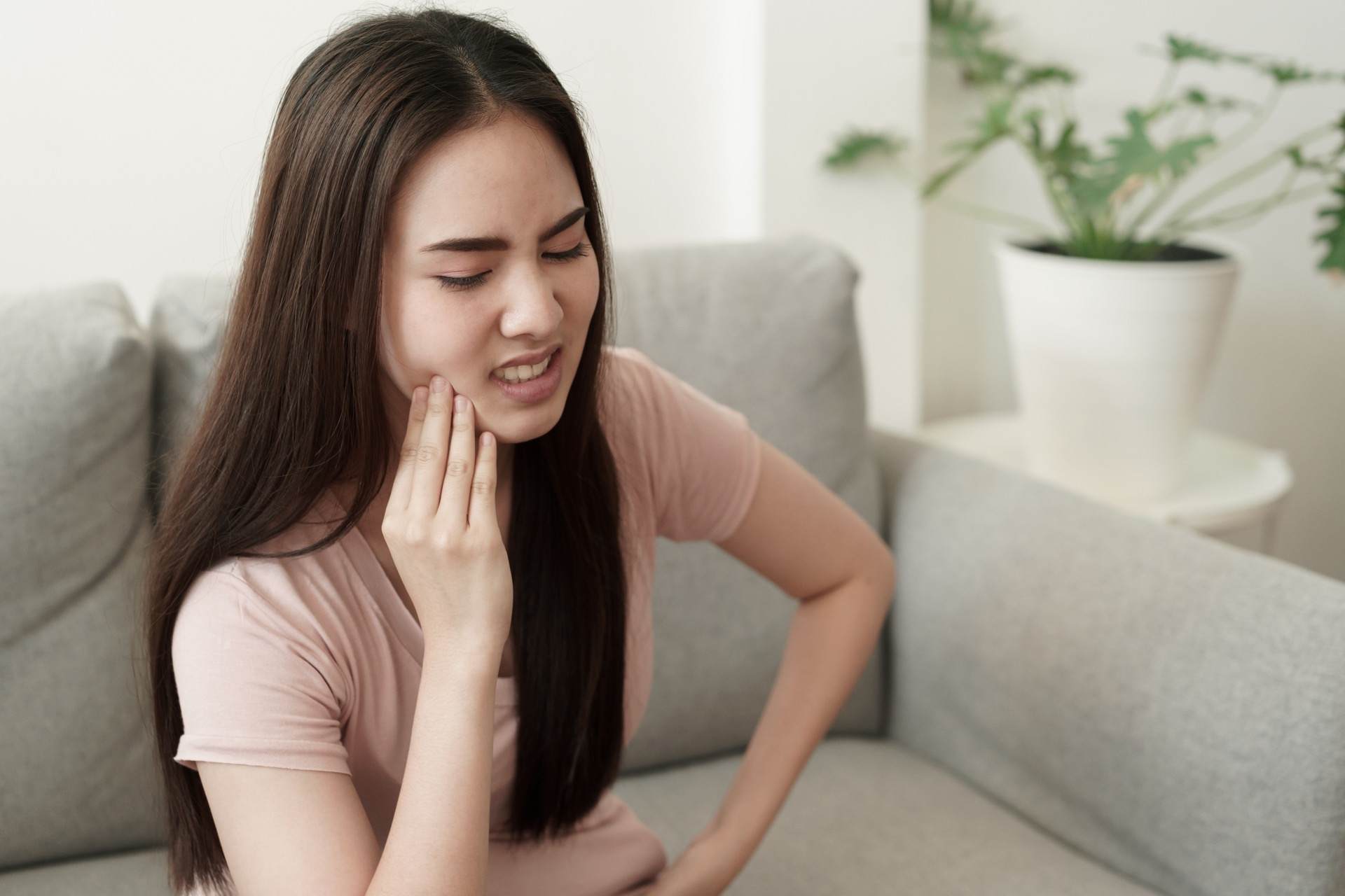 Asian woman with teeth sensitivity on couch at home