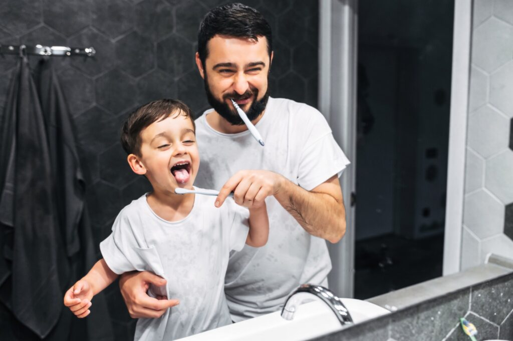 Father teaching his child the proper tooth-brushing technique
