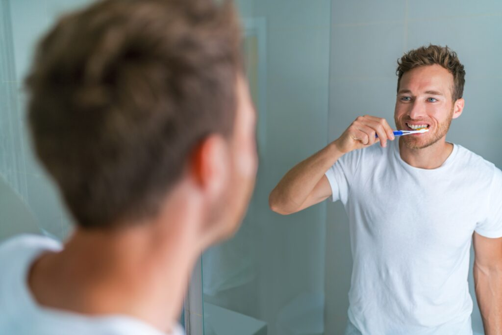 Man brushing sensitive teeth with soft toothbrush and sensitive toothpaste